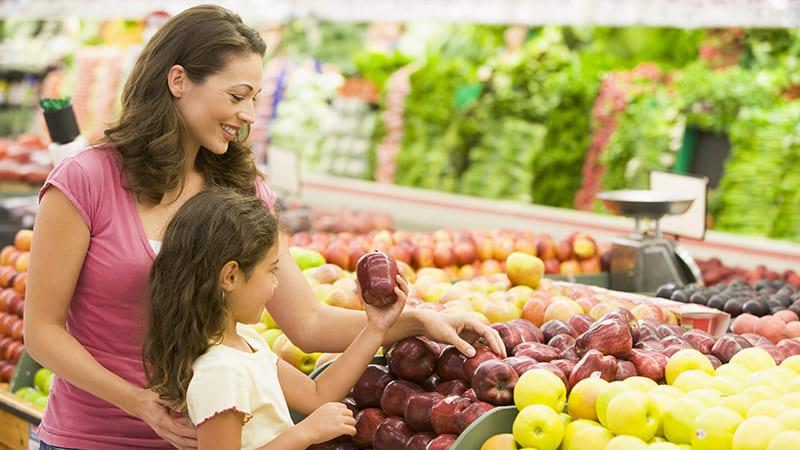 Выбирать фрукты и овощи в магазине