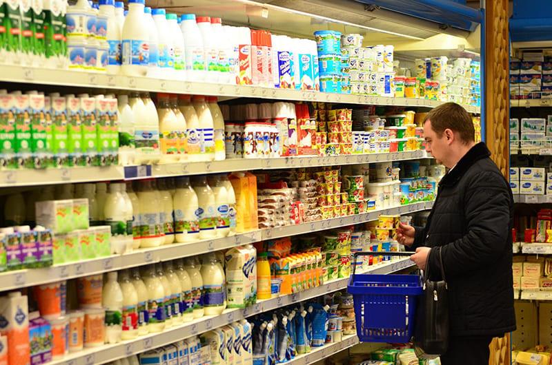 Выбирать молочные продукты в магазине