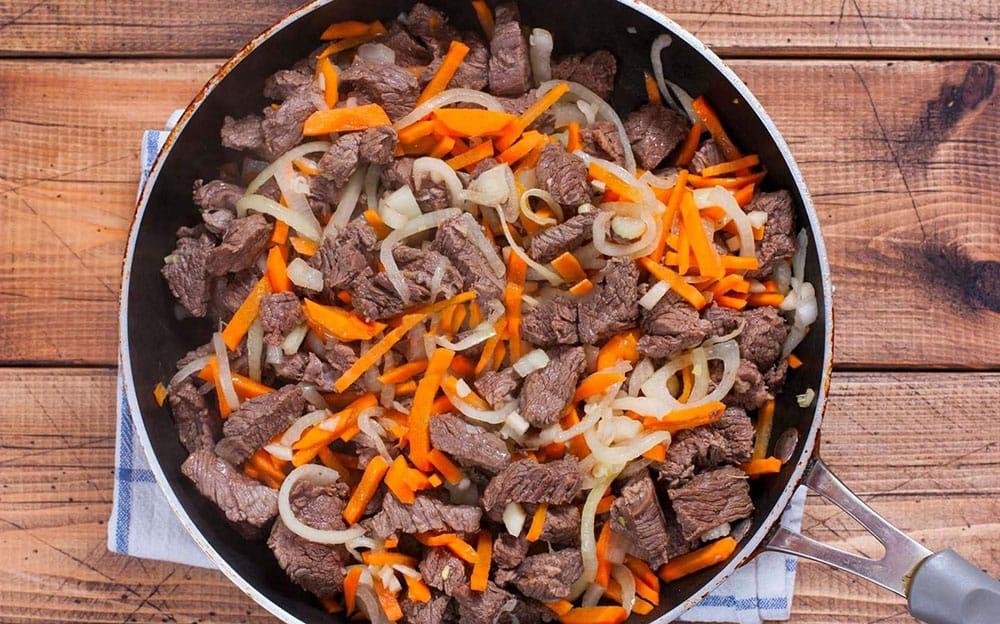 Говядина с луком и морковью на сковороде