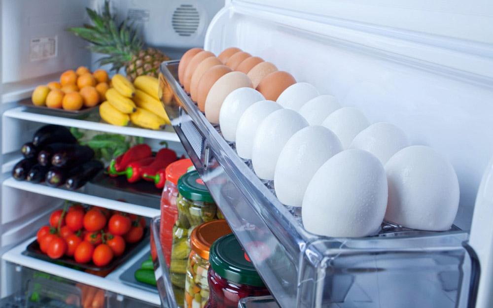Яйца и консервы на дверце холодильника
